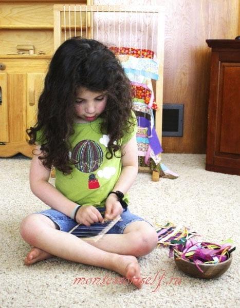 ребенок переплетает ленточки на ткацком станке