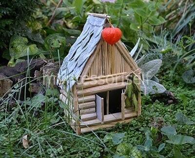 Картонный домик, украшенный палочками