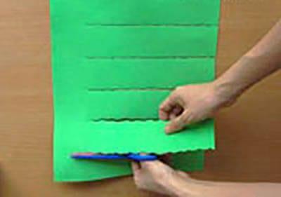 Надрезаем фигурными ножницами зеленую бумагу