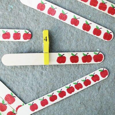 Количество яблок и число на прищепке