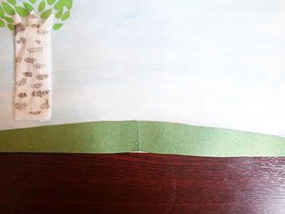 Приклеиваем холм из зеленой бумаги