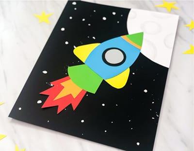 Открытка с ракетой и луной на День Космонавтики