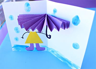 Приклеиваем фигурку девочки и рисуем дождь