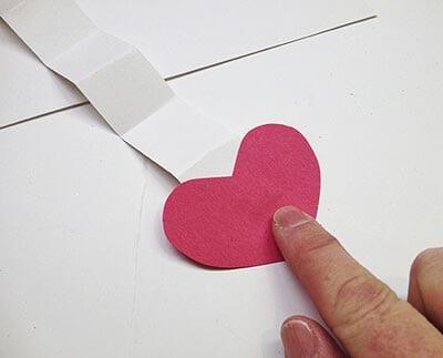 Приклеиваем сердечки на полоски-гармошки